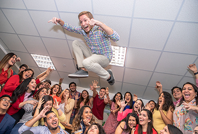 Man jumping in the air in front of a room of excited people