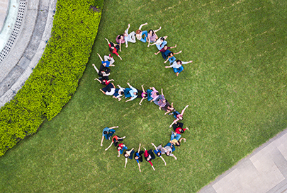 Aerial view of a group of people forming a letter S on a grassy lawn