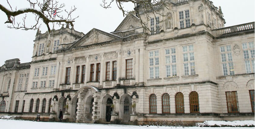 Cardiff university main building in the snow with a tree in the front