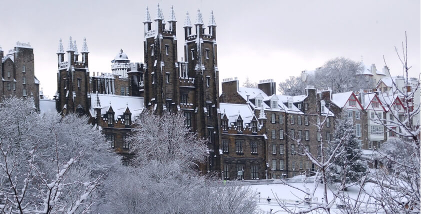Edinburgh University buiilding in the snow through snow covered trees