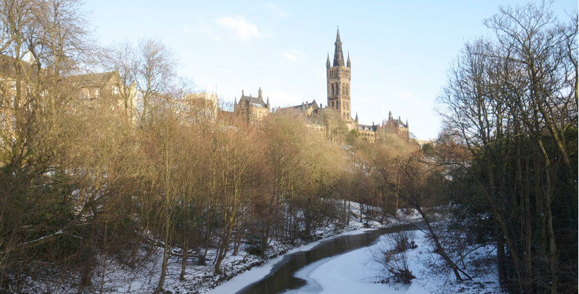 University of Glasgow in the distance with a stream surounded by trees in the snow