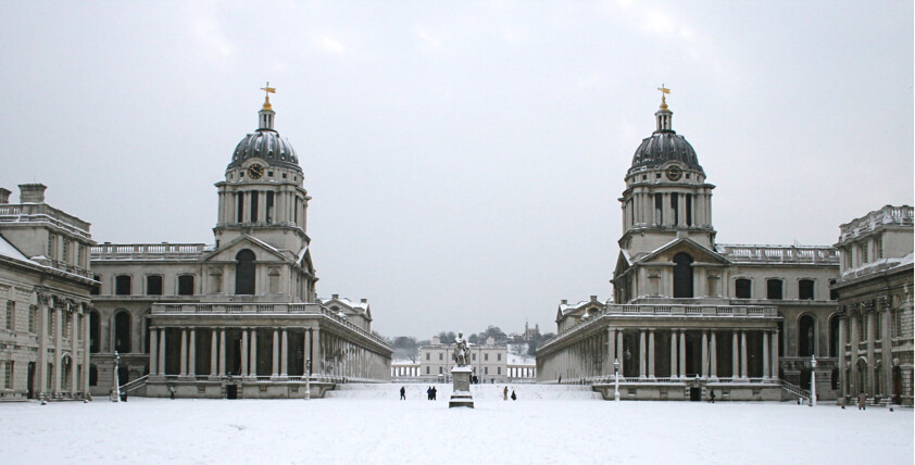 Greenwich university in the snow with a statue between the two buildings