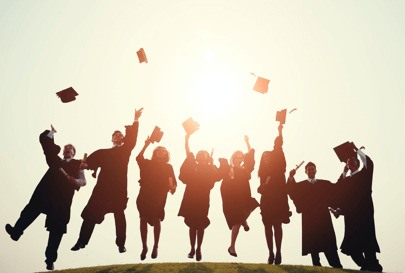 Graduates throwing their hats in the air, wearing black graduate gowns